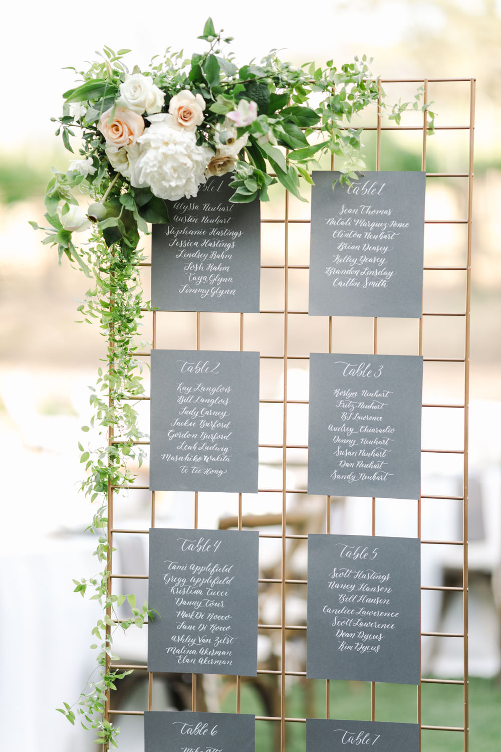 Wedding escort seating chart with white calligraphy on grey square paper on metallic stand with white and green flowers, Cavin Elizabeth Photography