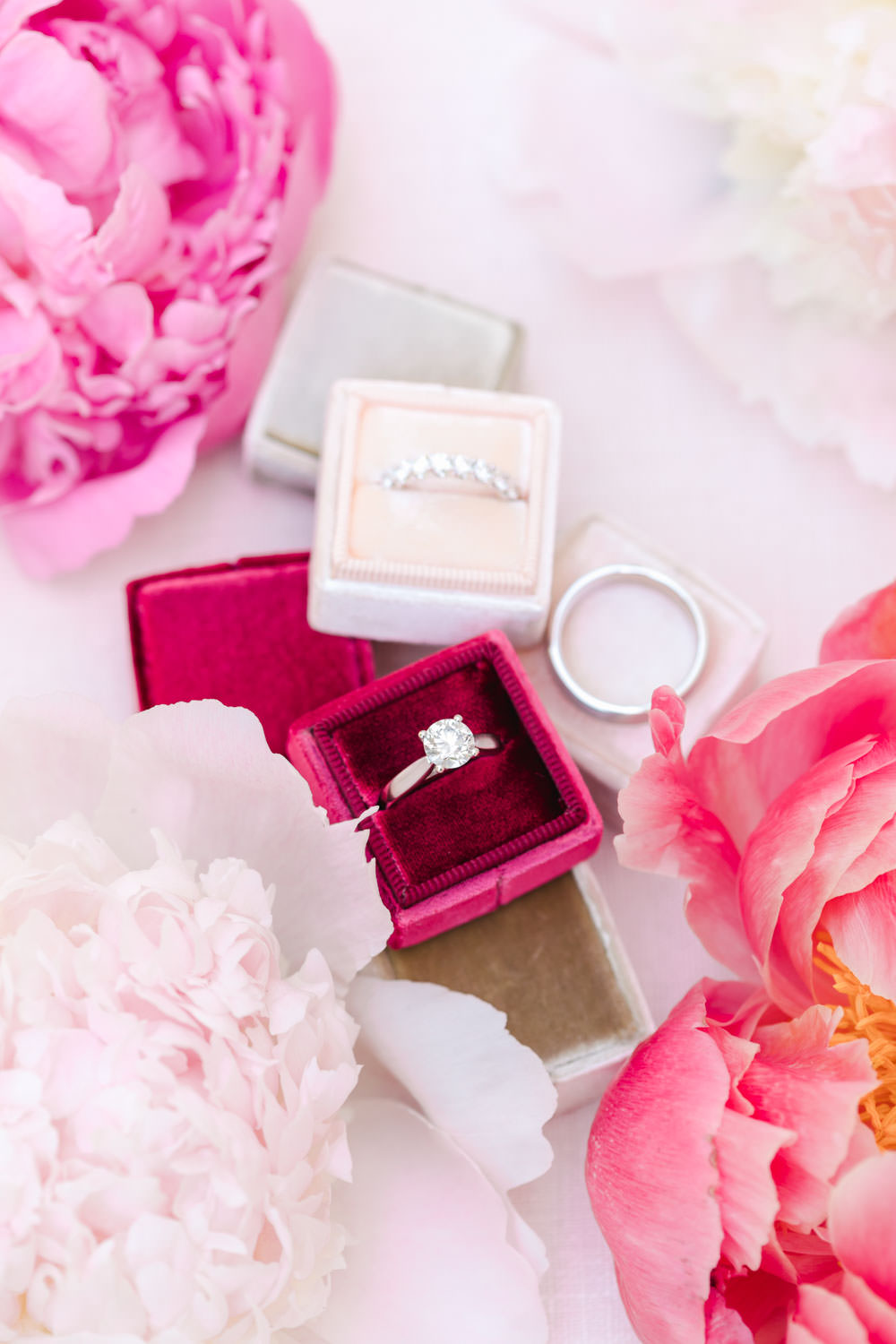 Engagement and wedding rings in different colors of Mrs Boxes velvet ring boxes styled with flowers, Cavin Elizabeth Photography