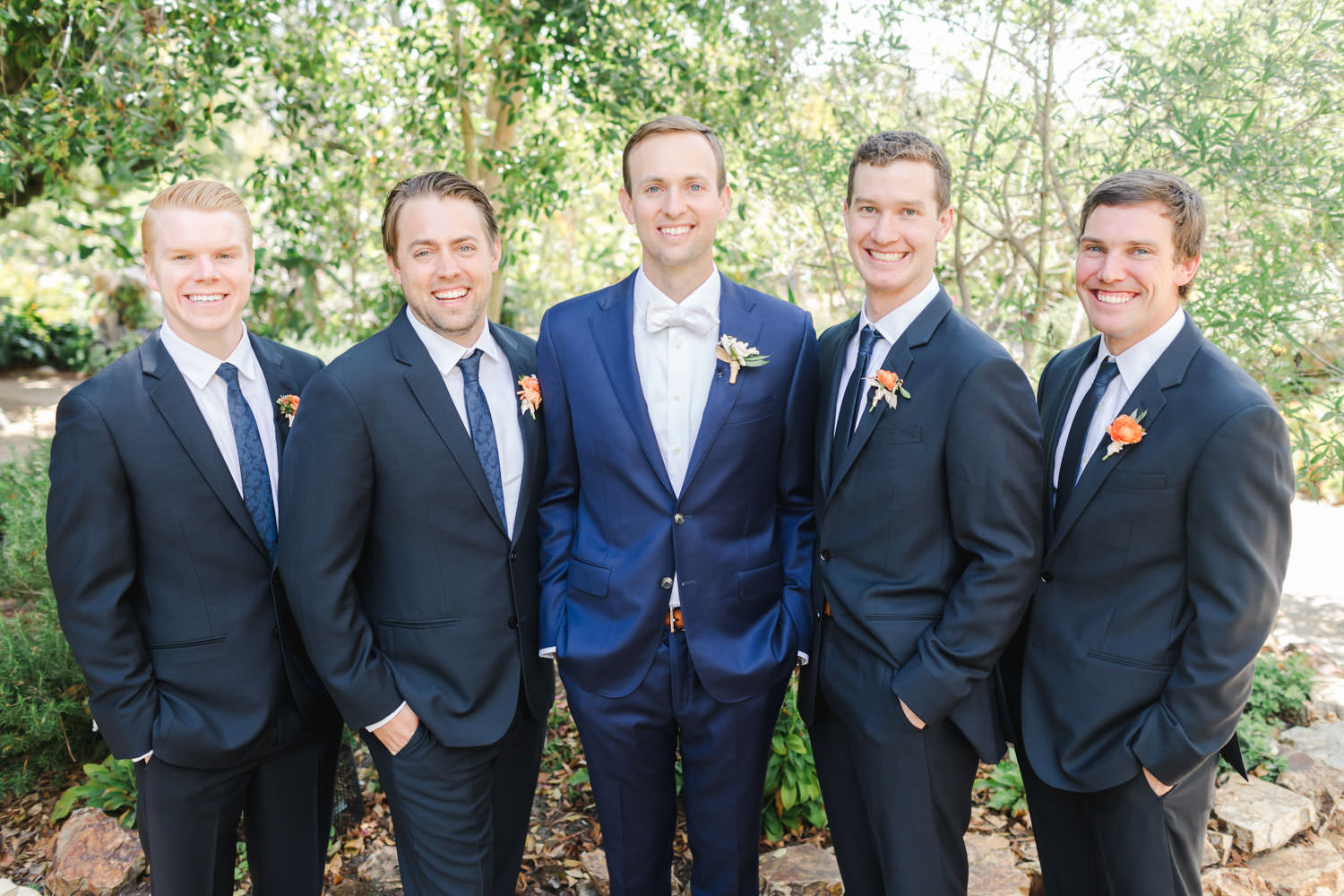 Groom in navy with groomsmen in black suits for a San Diego Botanic Garden wedding with blue and pink colors, Cavin Elizabeth Photography