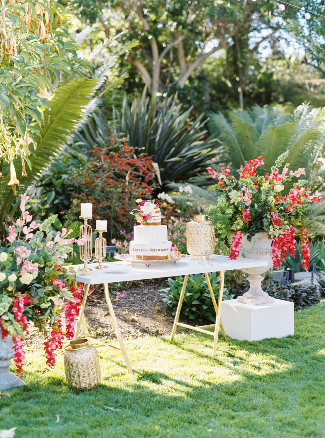 Wedding cake on white and gold table surrounded by floral arrangements with bougainvillea, Cavin Elizabeth Photography