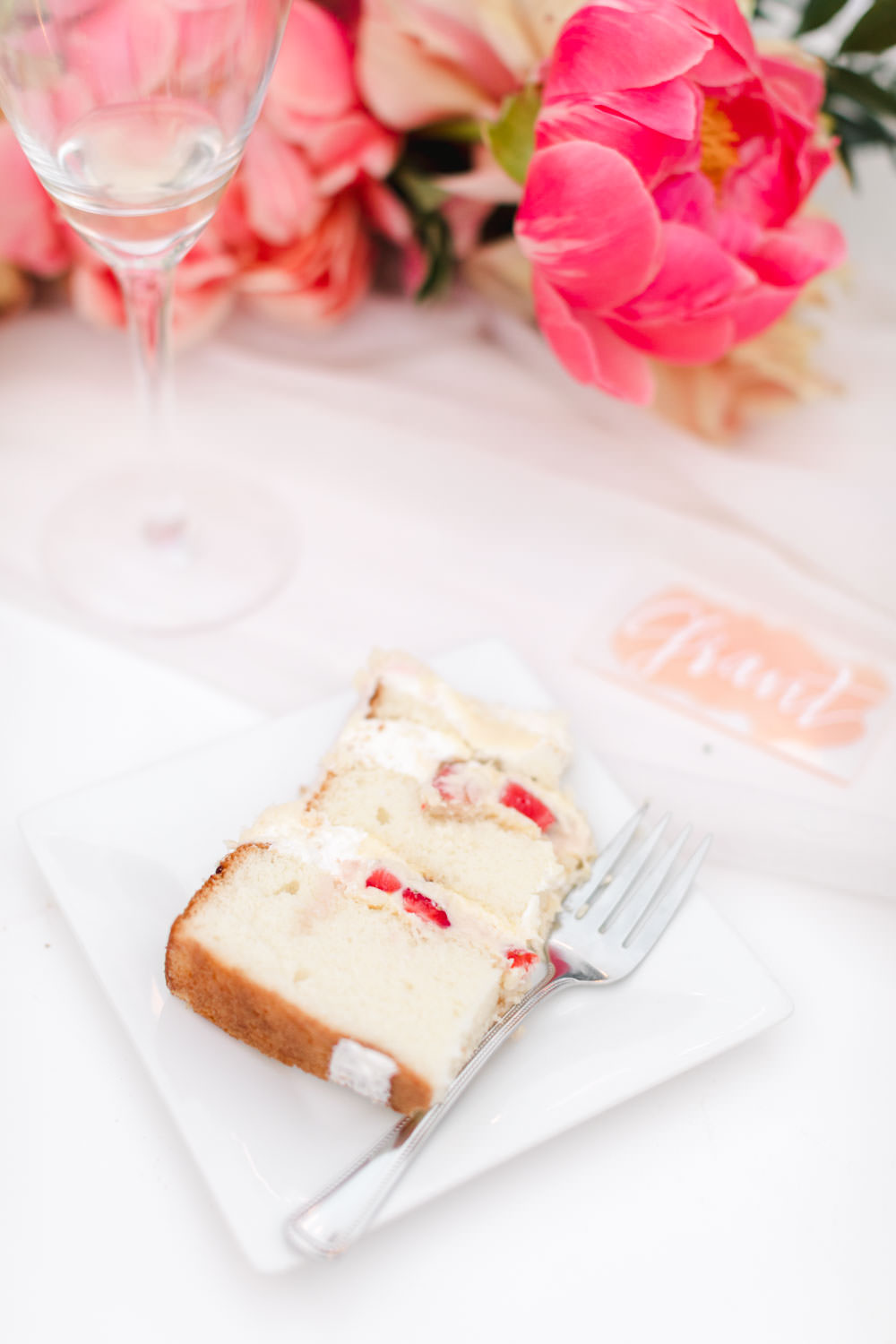 White cake with strawberry cream filling in front of pink flowers, Cavin Elizabeth Photography