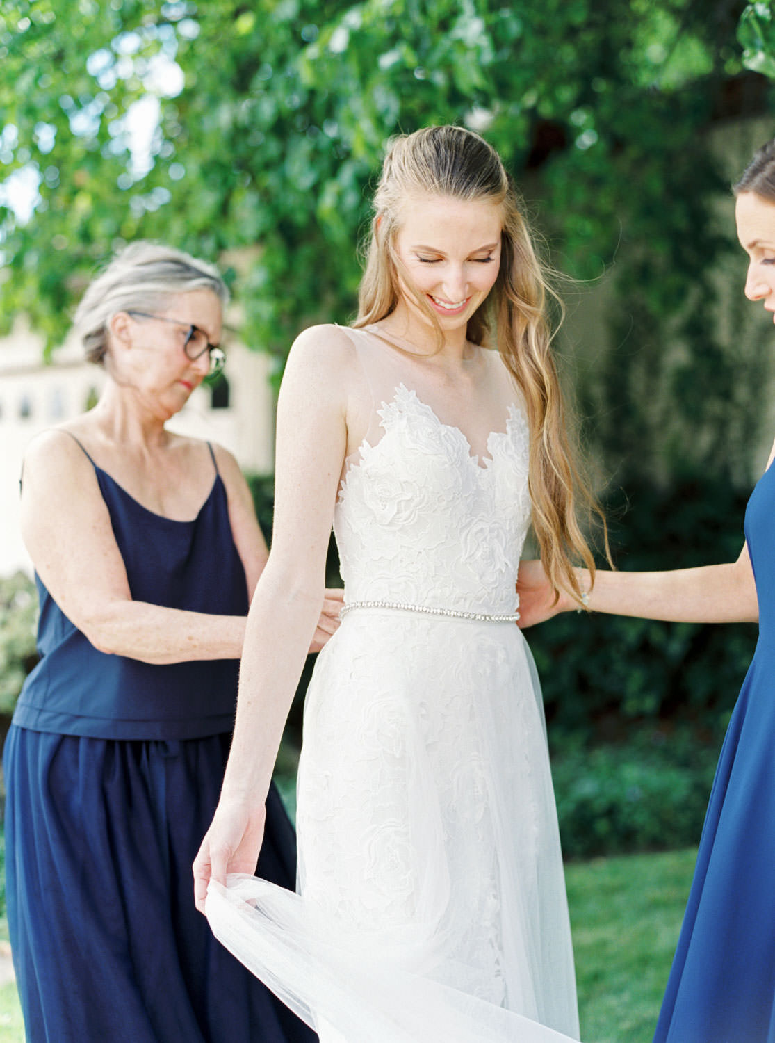 Bride getting into wedding dress outside with mom and sister captured on film, Cavin Elizabeth Photography