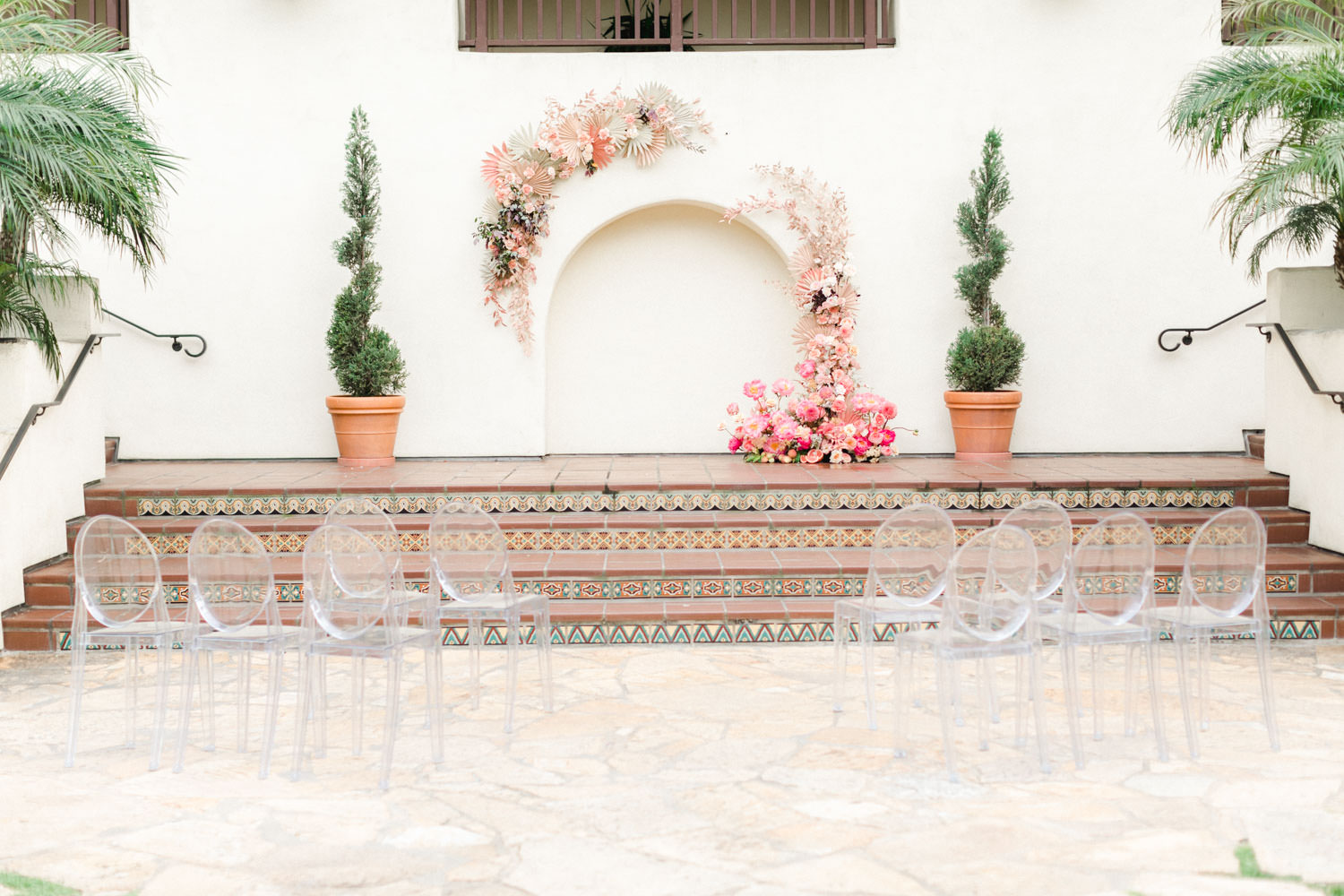 Pink peach and white floral installation over an archway with ghost chairs, Wedding at Estancia La Jolla, Cavin Elizabeth Photography