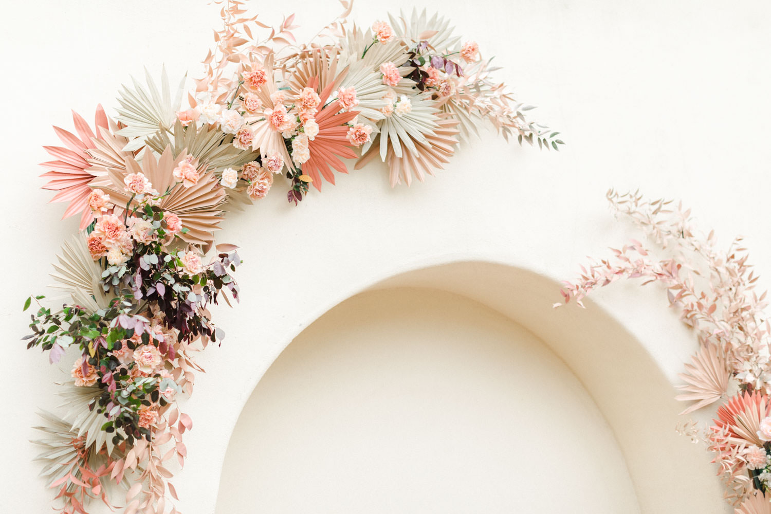 Paper fans in terracotta beige and pink, Pink peach and white floral installation over an archway with ghost chairs, Wedding at Estancia La Jolla, Cavin Elizabeth Photography