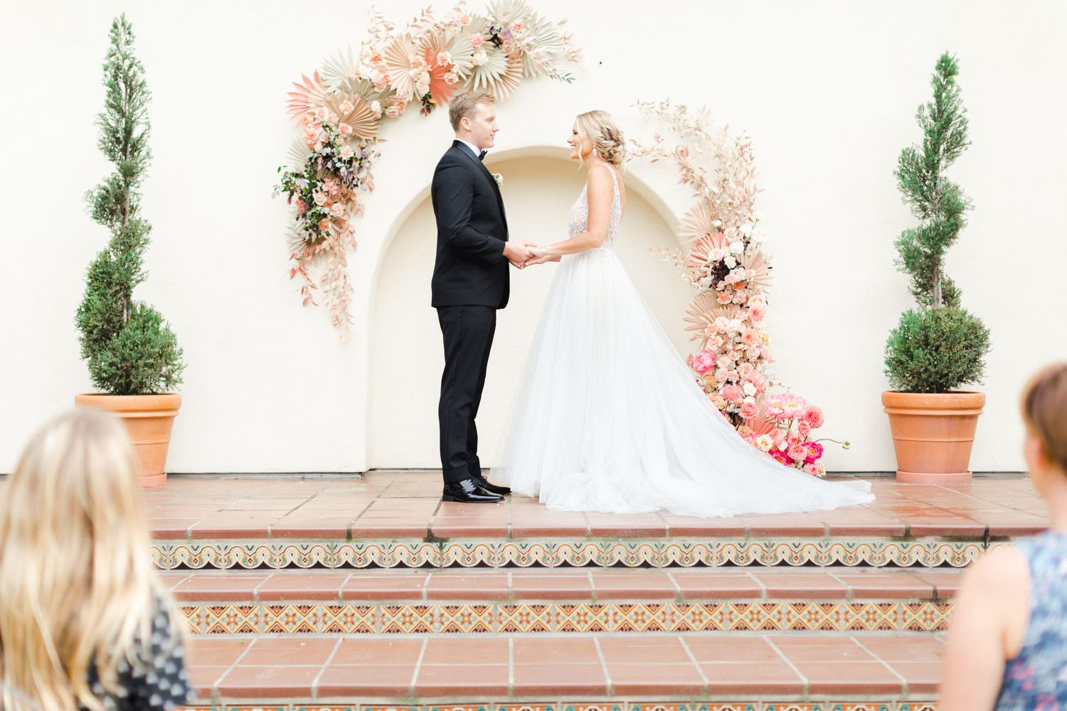 Ceremony vows in front of Pink peach and white floral installation over an archway with ghost chairs, Wedding at Estancia La Jolla, Cavin Elizabeth Photography