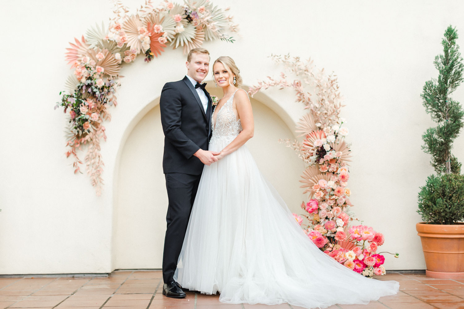 Bride and groom in front of Pink peach and white floral installation over an archway with ghost chairs, Wedding at Estancia La Jolla, Cavin Elizabeth Photography