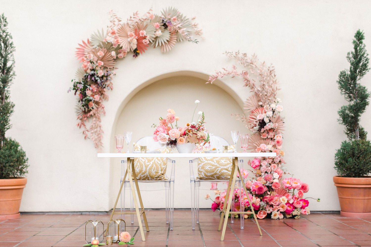 Sweetheart white table with pink and peach floral arrangements and a pink floral installation backdrop, Cavin Elizabeth Photography