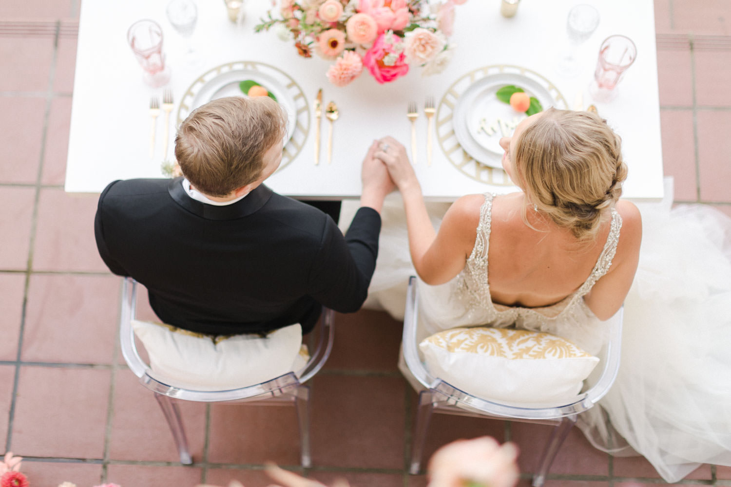 Bride and groom holding hands at Sweetheart white table with pink and peach floral arrangements and a pink floral installation backdrop, Cavin Elizabeth Photography