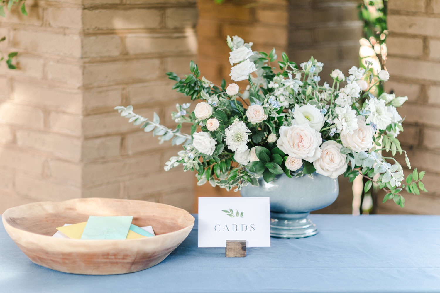 Gift table with white peach and green floral arrangement and blue linen, Cavin Elizabeth Photography