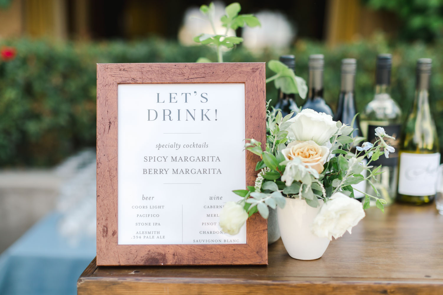 Cocktail menu with white peach and green floral arrangement and blue linen, Cavin Elizabeth Photography