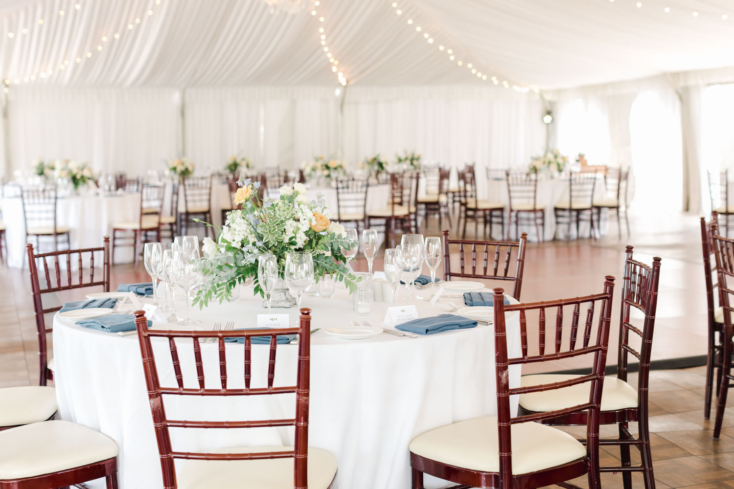 Santaluz Club wedding tented reception with blue napkins and peach green and white flower arrangement centerpieces, Cavin Elizabeth Photography