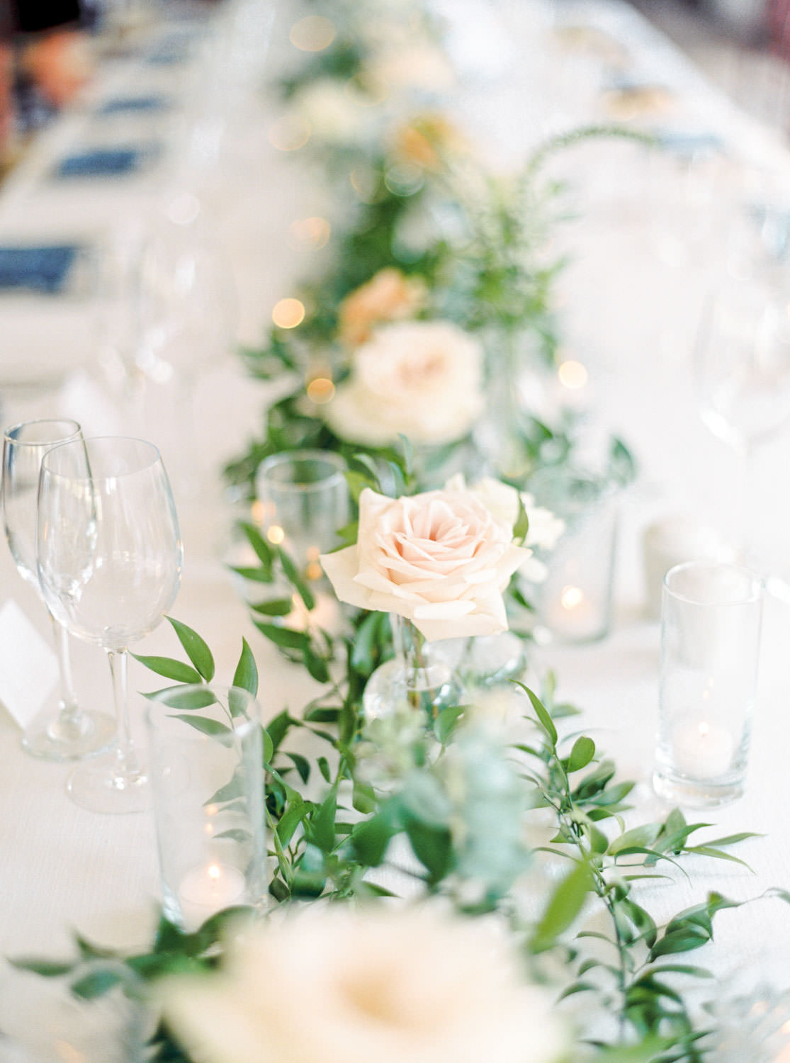 Film image of Santaluz Club wedding tented reception with blue napkins and peach green and white flower arrangement centerpieces, Cavin Elizabeth Photography