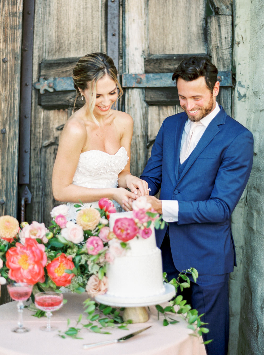 Film image of cutting Two tier white wedding cake with coral charm peonies and yellow and blush flowers, Cavin ELizabeth Photography
