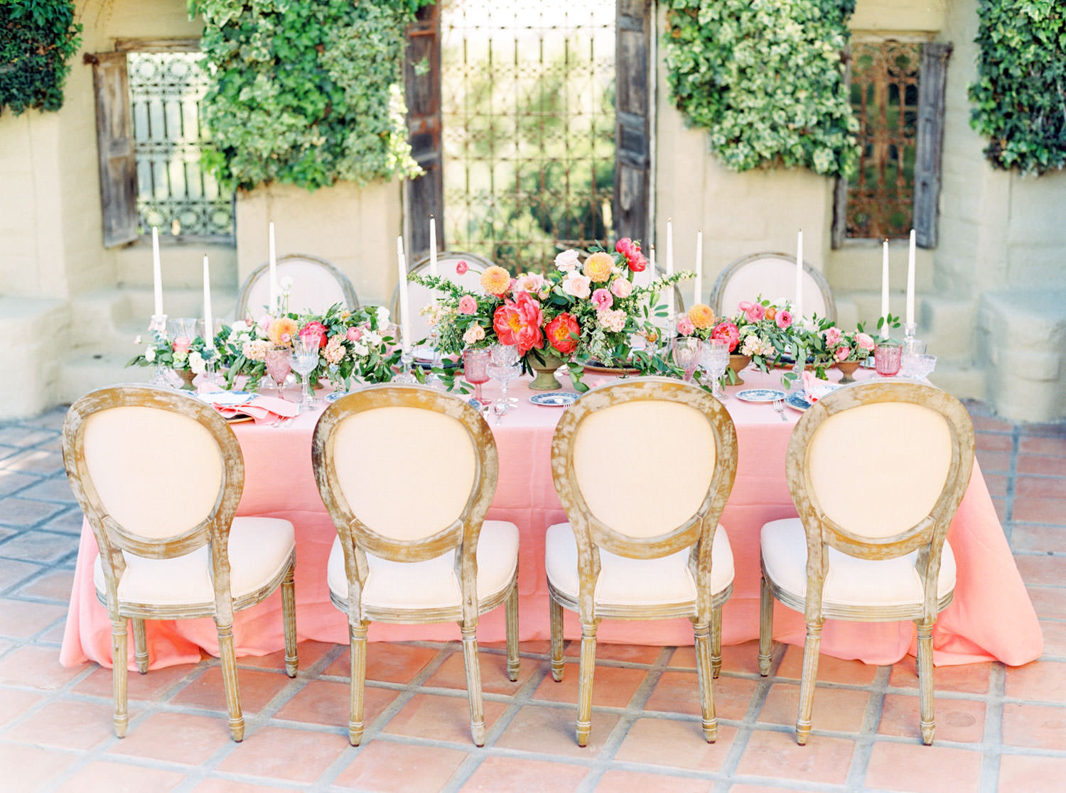 Film photo of table with oak louies and a pink coral linen with green pink and yellow flowers, Whispering Rose Ranch Press published on Style Me Pretty by Cavin Elizabeth Photography