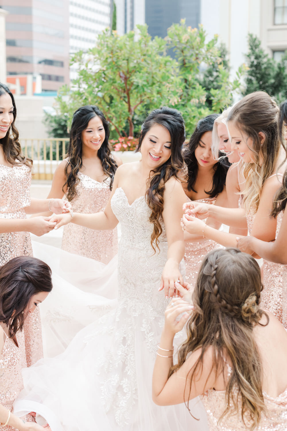 Bridesmaids in blush sequin gowns helping bride into her wedding gown on a rooftop at the Westgate Hotel in San Diego, Cavin ELizabeth Photography