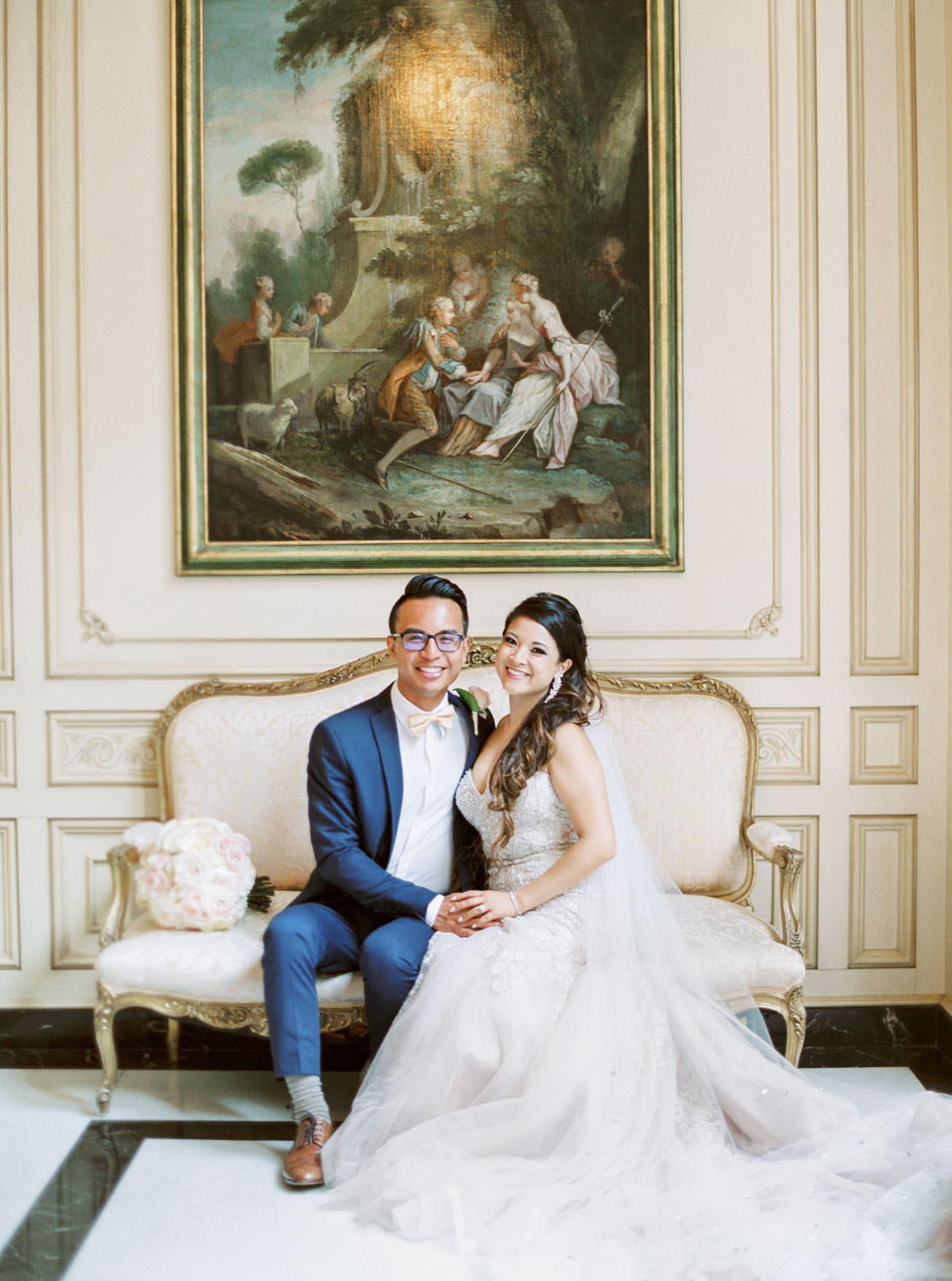 Bride and groom on a vintage sofa under a fine art painting at the Elegant Westgate Hotel Wedding in Downtown San Diego, Cavin Elizabeth Photography