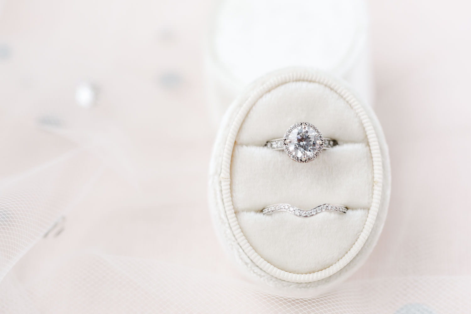 Diamond engagement ring with halo and wedding band with pave diamonds in an ivory oval velvet ring box, Cavin ELizabeth Photography