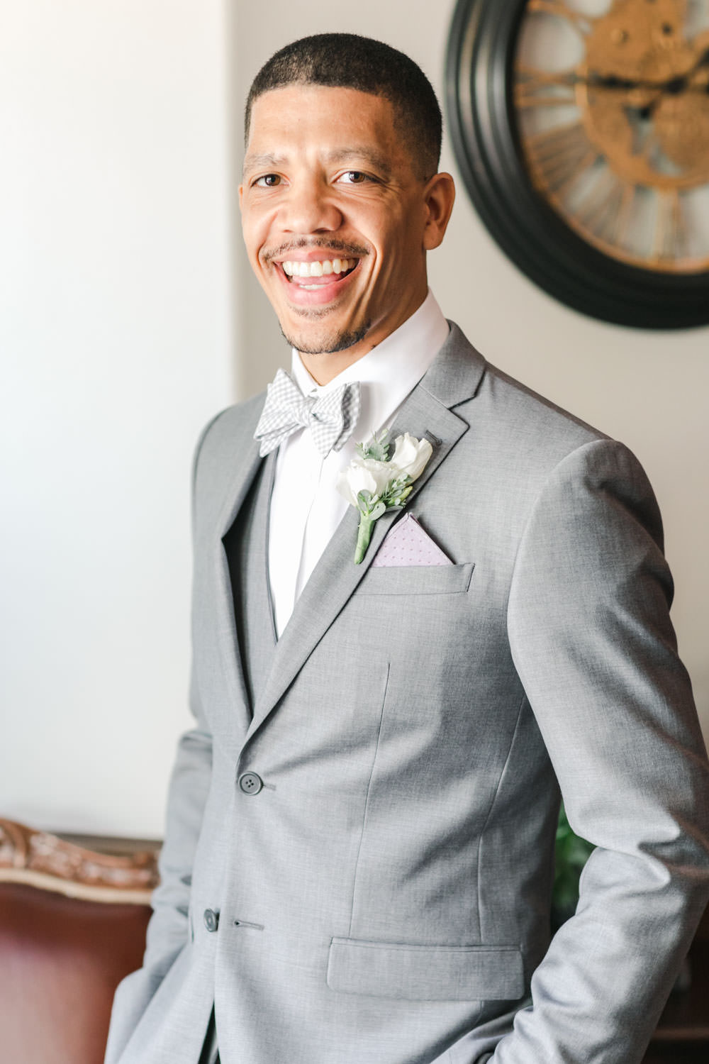 Portrait of groom getting ready in his grey tux with white and green boutonniere, Cavin Elizabeth Photography