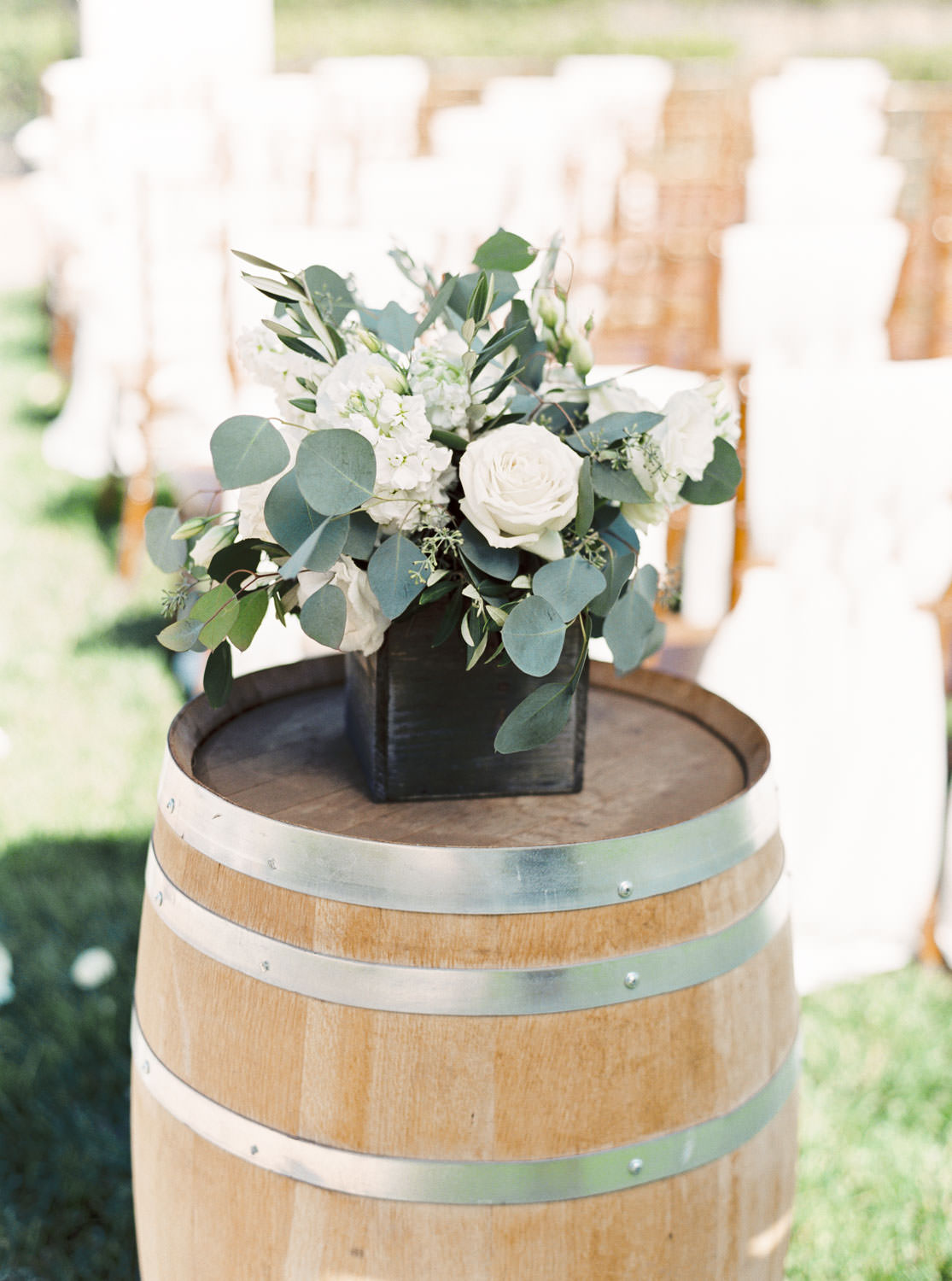 White and green centerpieces on a barrel for ceremony decorations, Cavin Elizabeth Photography