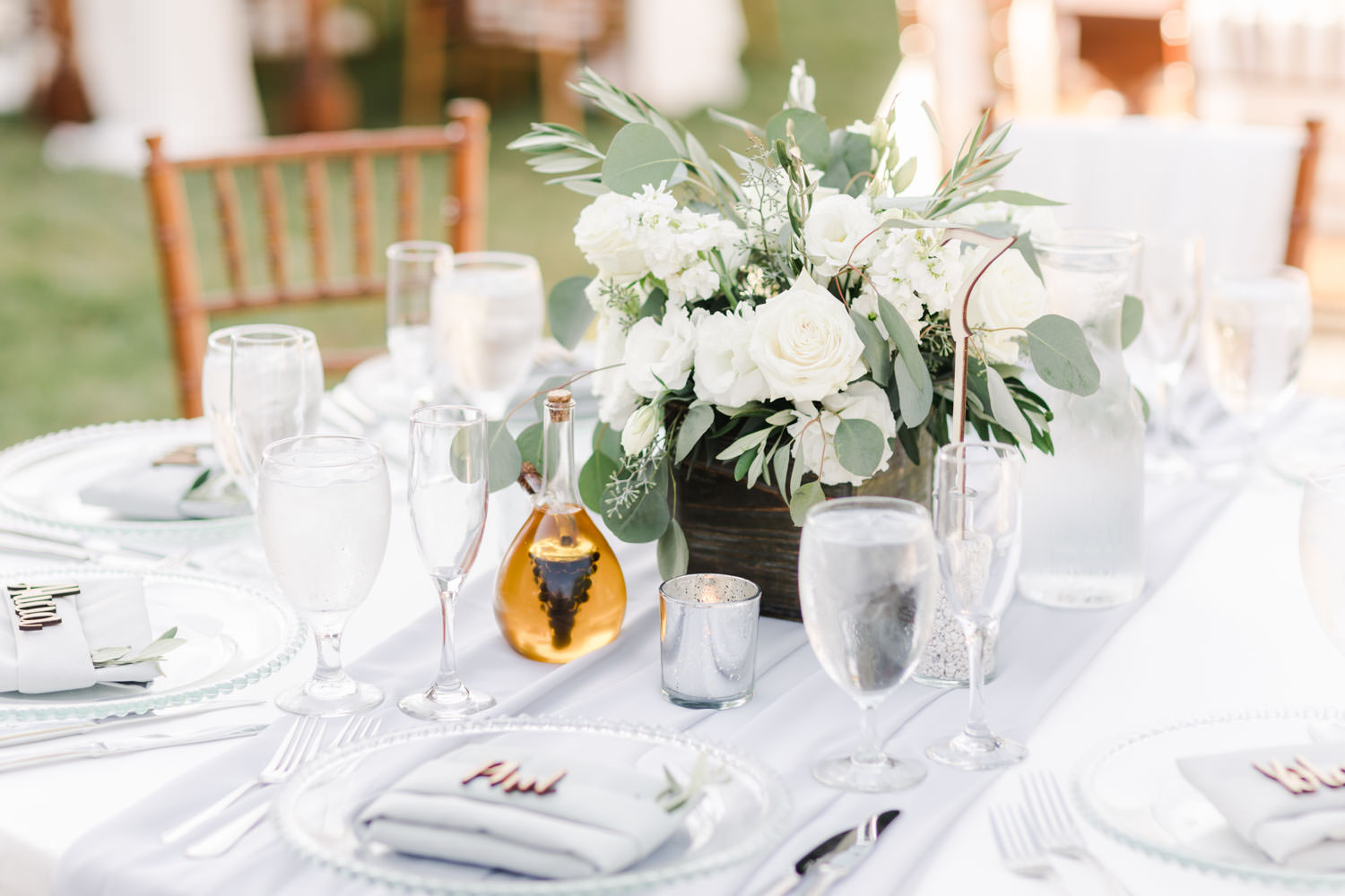 Green and white centerpiece with clear beaded charger with grey napkin and wood laser cut name card at Temecula Wedding at Villa De Amore, Cavin Elizabeth Photography