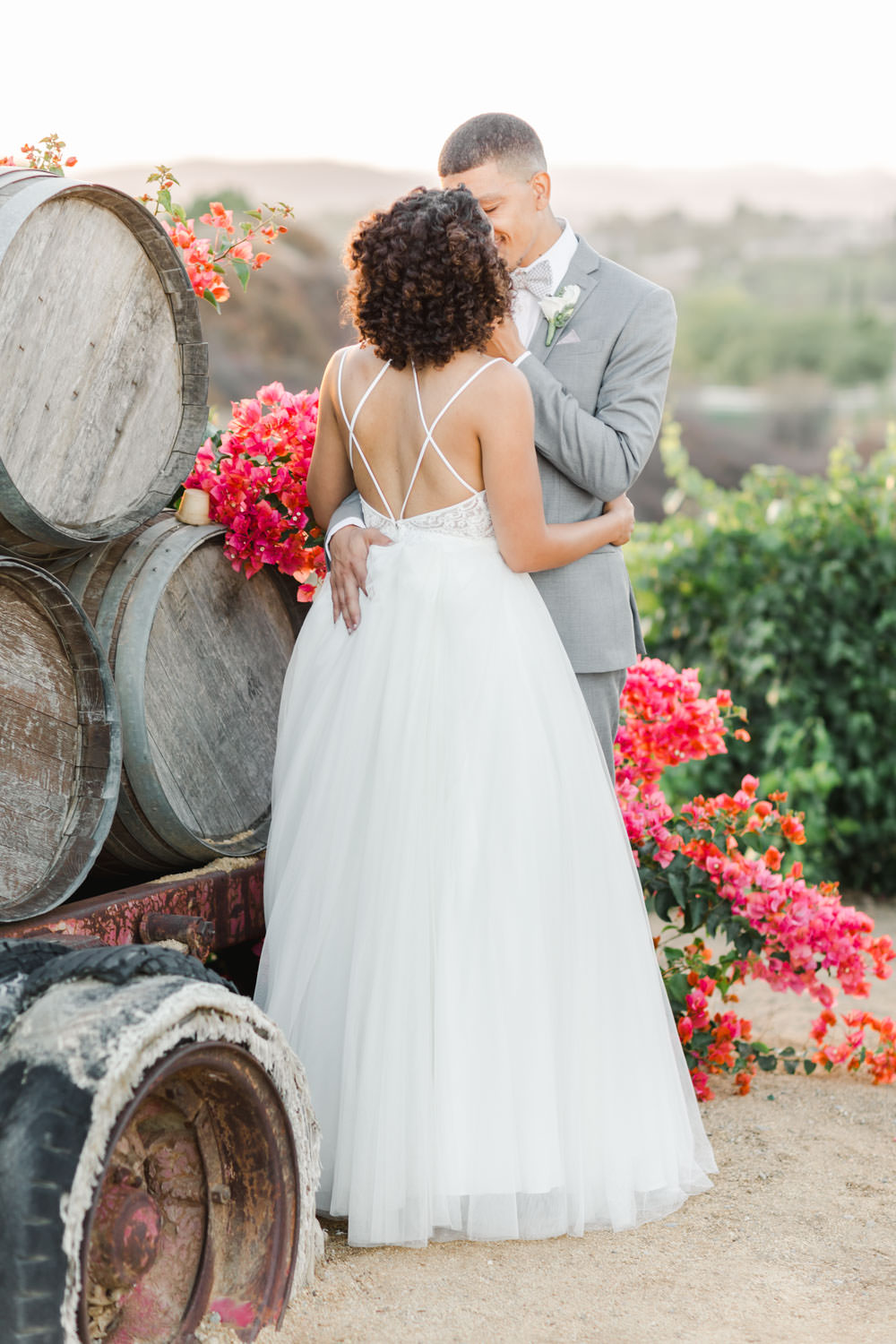 Bride and groom in front of pink bougainvillea and barrels, Cavin ELizabeth Photography