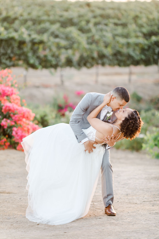 Bride and groom dip portrait in front of pink bougainvillea, Cavin Elizabeth Photography