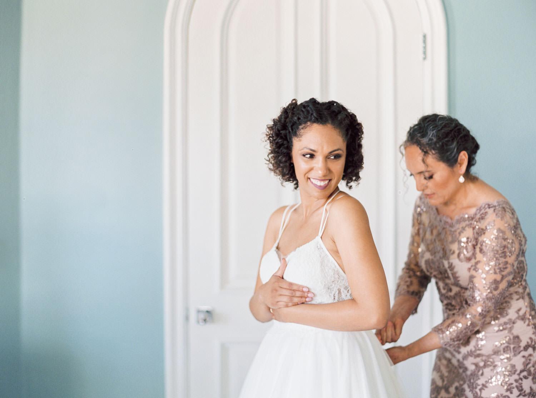 Film portrait of a bride getting into her wedding gown, Cavin Elizabeth Photography
