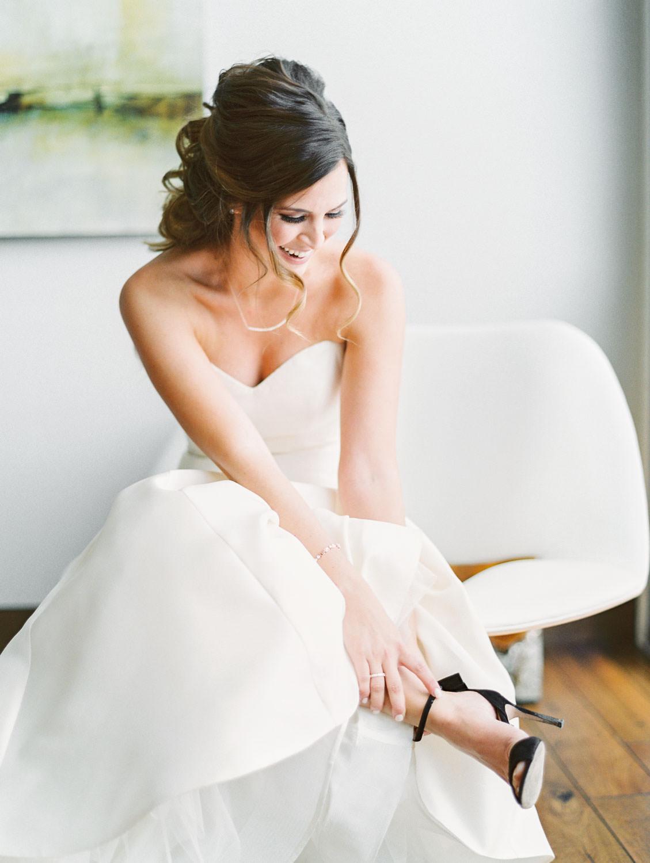 Bride putting on black Valentino heels, film photo by Cavin Elizabeth Photography