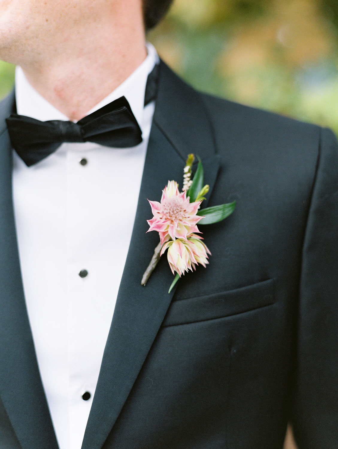 Groom boutonniere with pink and green on black tux at Green Acre Campus Pointe Wedding, film photo by Cavin Elizabeth Photography