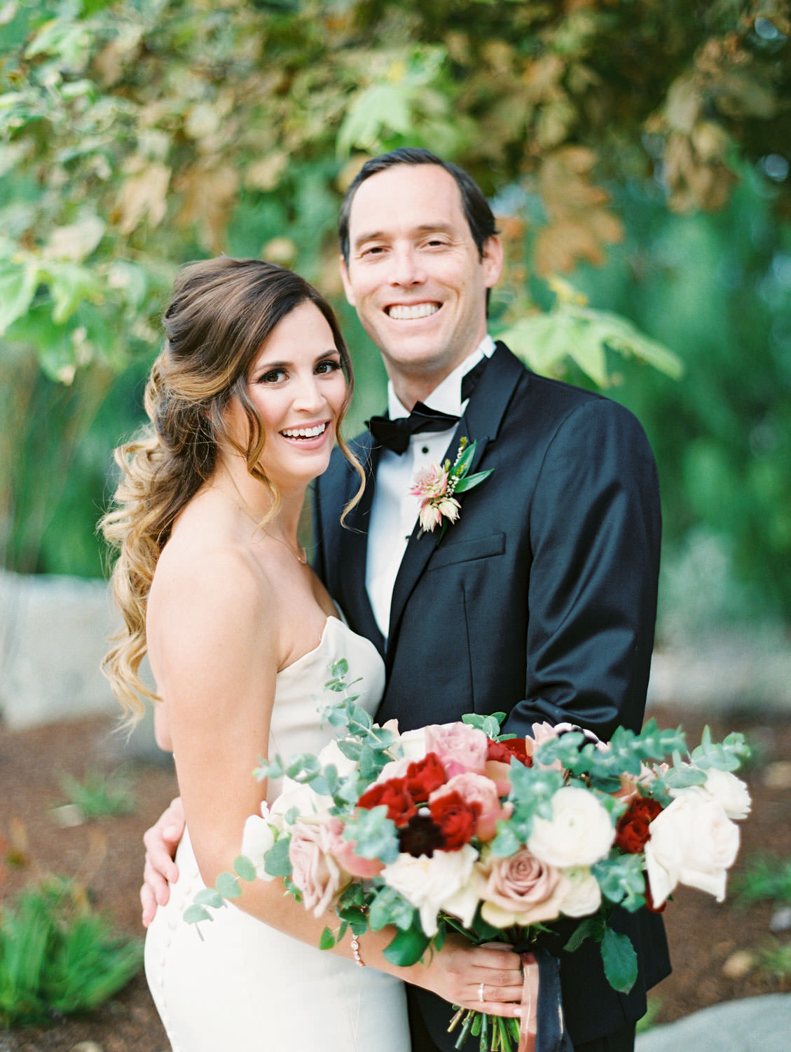 Bride in Anne Barge sweetheart gown with red ivory and mauve bouquet and groom in black tux smiling at camera at Green Acre Campus Pointe Wedding, film photo by Cavin Elizabeth Photography