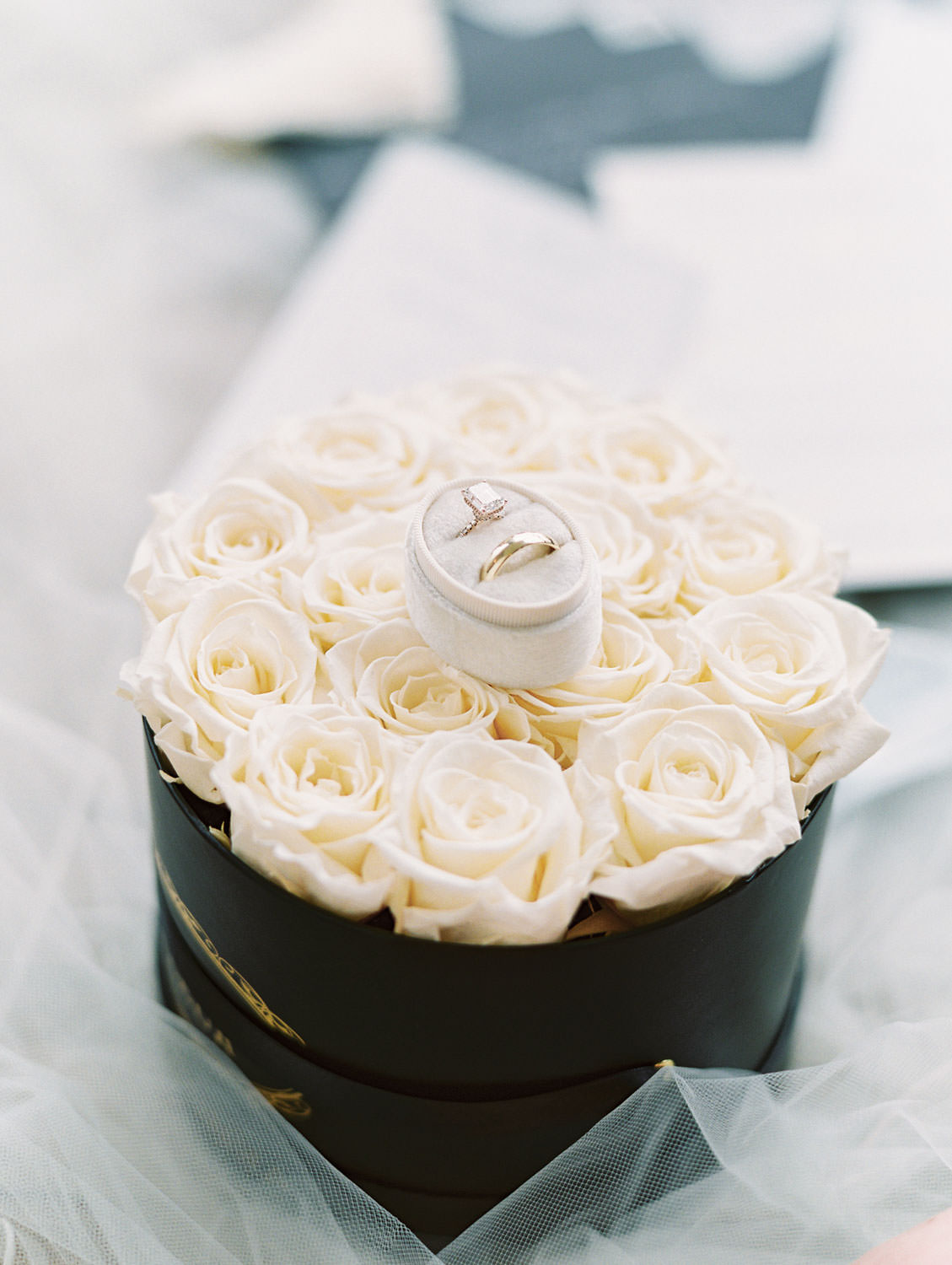 Wedding rings in oval velvet ring box on top of roses, film photo by Cavin Elizabeth Photography