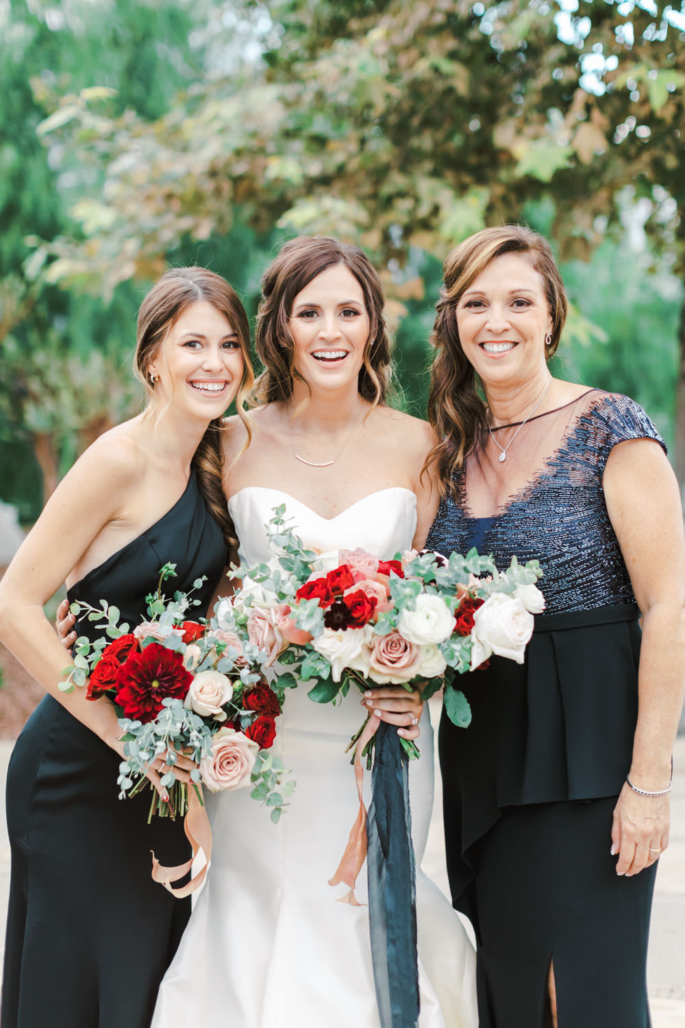Bride with sister and mom on the wedding day with mauve red and ivory bouquets and navy ribbons, Cavin Elizabeth Photography