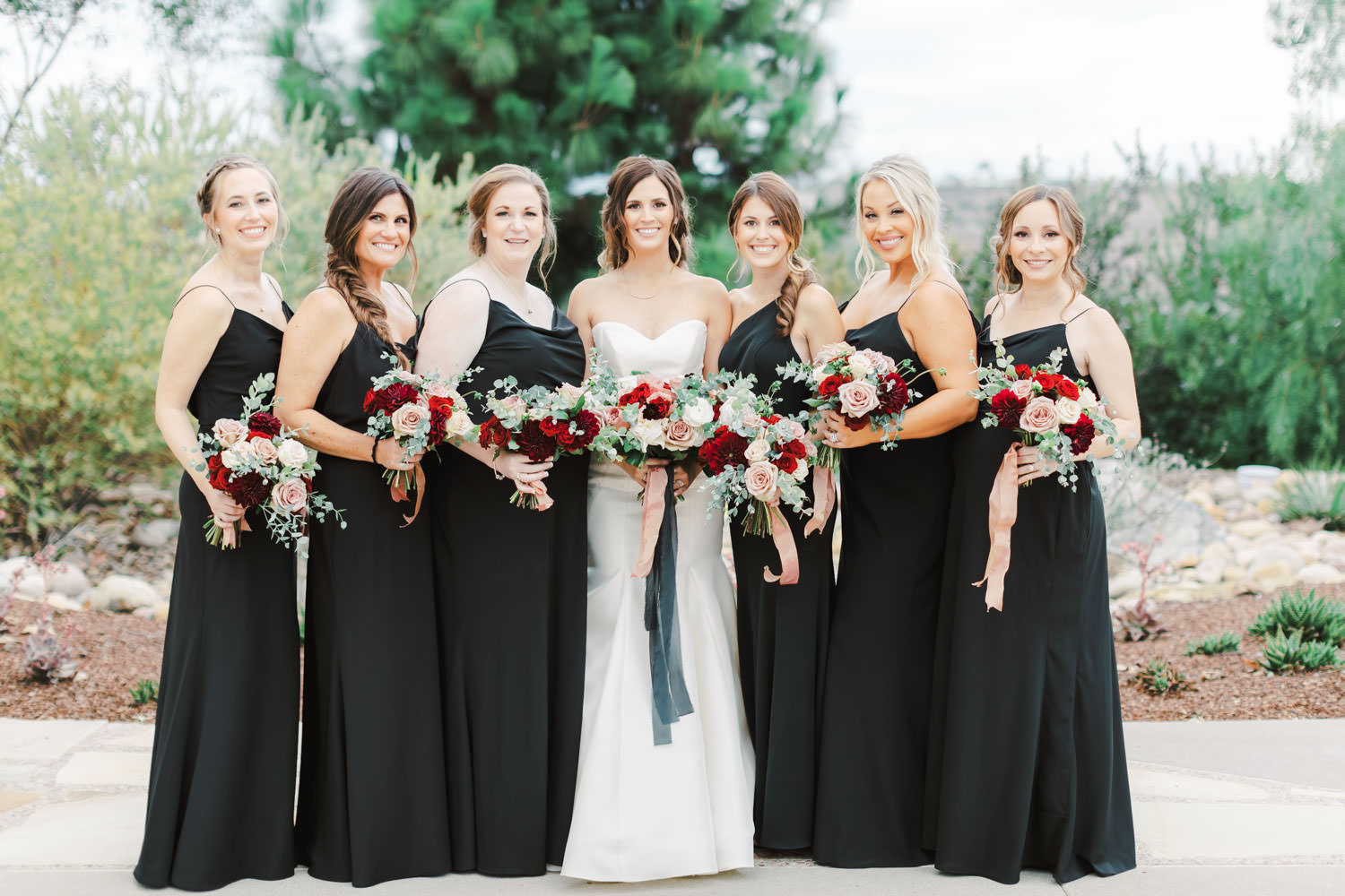 Bride in Anne Barge sweetheart gown with red ivory and mauve bouquet and bridesmaids in black dresses at Green Acre Campus Pointe Wedding, photo by Cavin Elizabeth Photography
