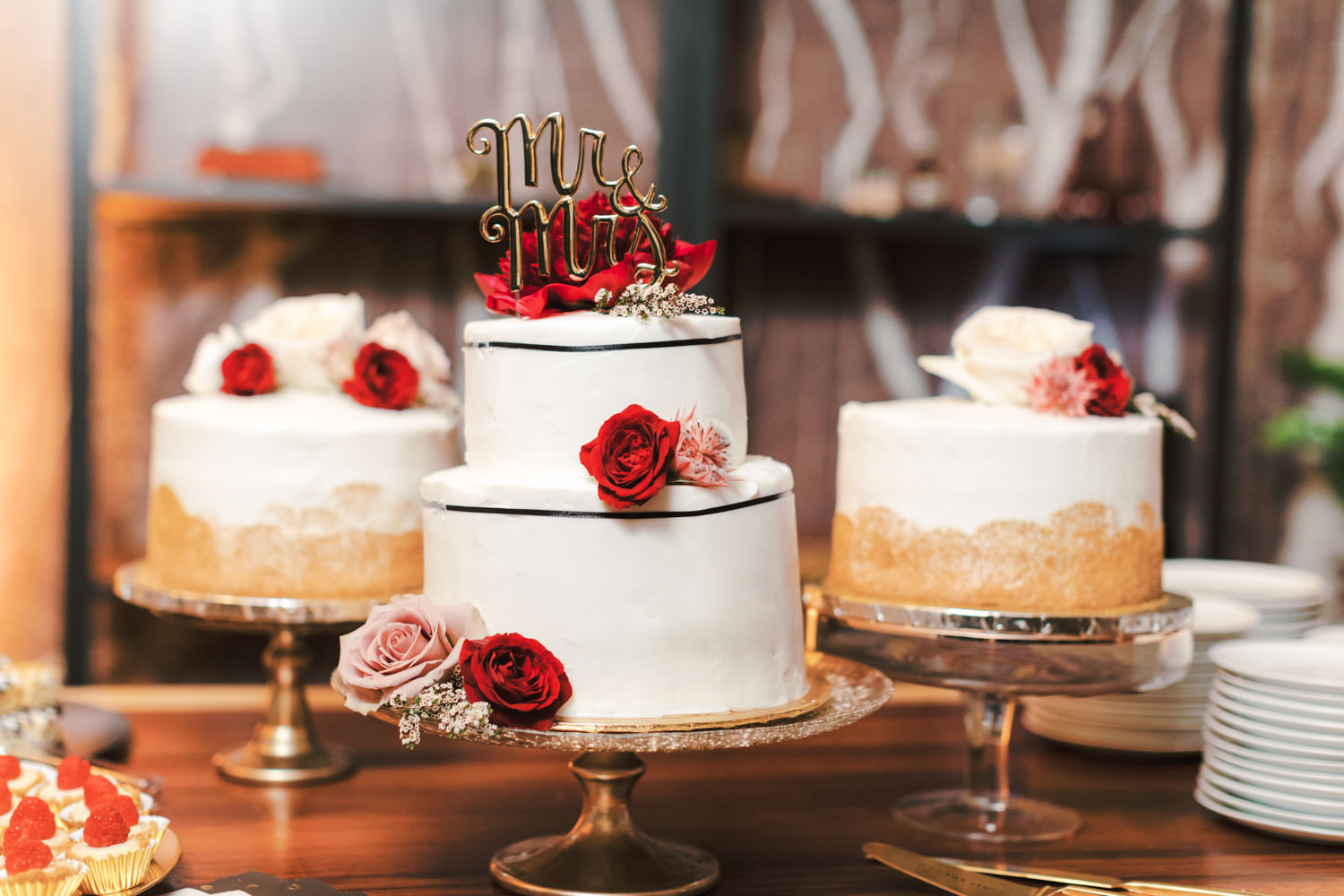 Two tier white wedding cake with small black ribbons and red and mauve roses and mr and mrs topper, Green Acre Campus Pointe Wedding San Diego, Cavin Elizabeth Photography