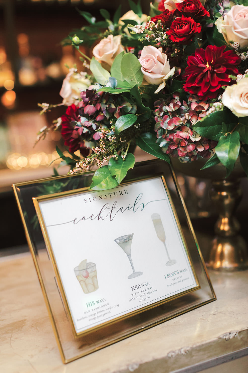 Cocktail bar floral arrangement and custom watercolor cocktail menu with red mauve green and ivory, Green Acre Campus Pointe Wedding San Diego, Cavin Elizabeth Photography
