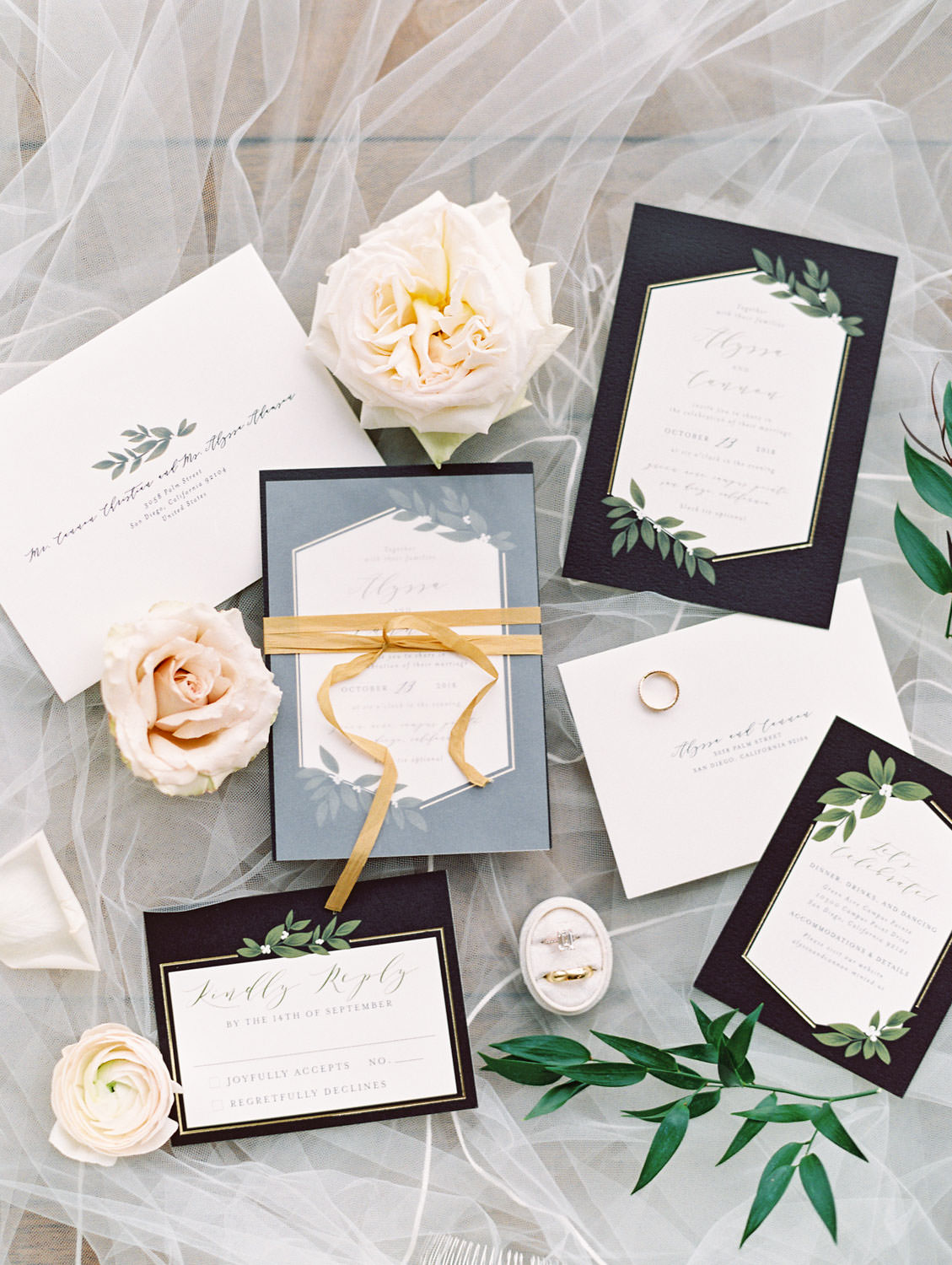 Black and white wedding invitation suite with greenery illustration and gold ribbon styled with flowers and rings, film photo by Cavin Elizabeth