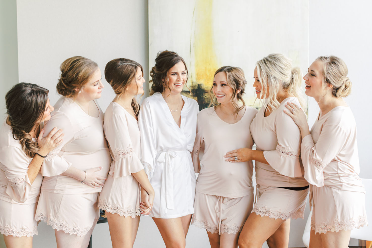Bride in white robe and bridesmaids in light pink pajamas before the wedding, Cavin Elizabeth Photography