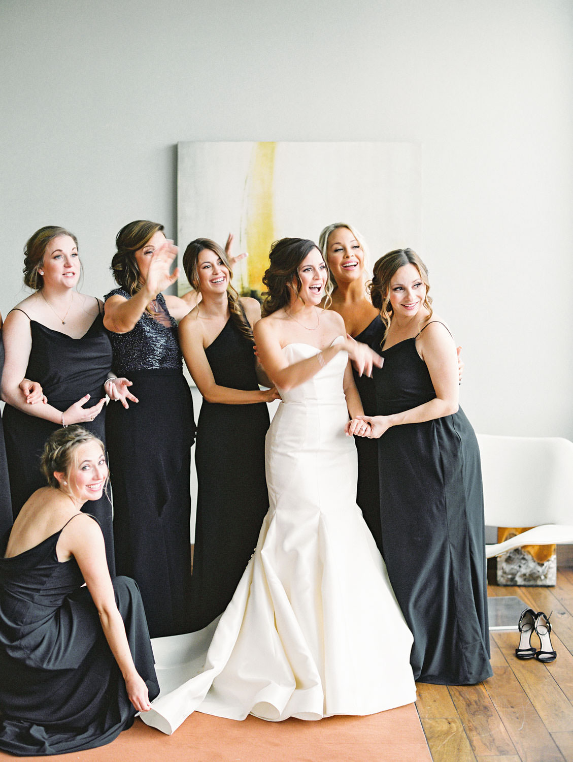 Bride getting into wedding gown with bridesmaids, film photo by Cavin Elizabeth Photography