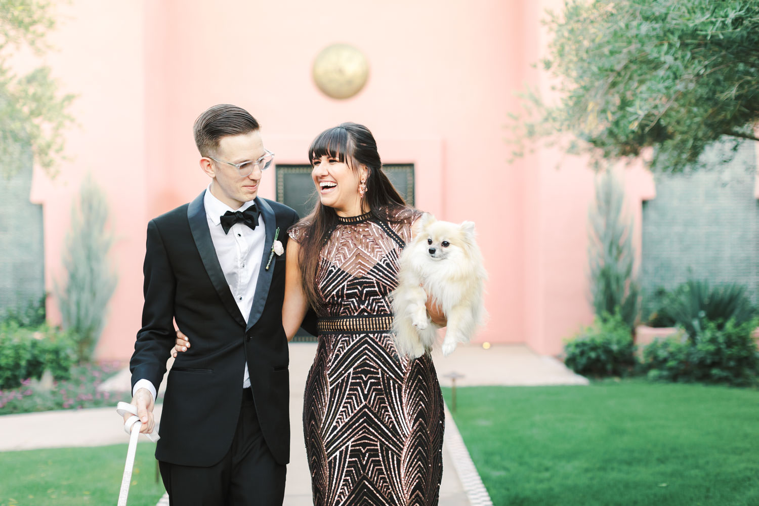 Image of bride and groom with dogs in front of the pink entrance to Sands Hotel spa in Indian Wells, Cavin Elizabeth Photography