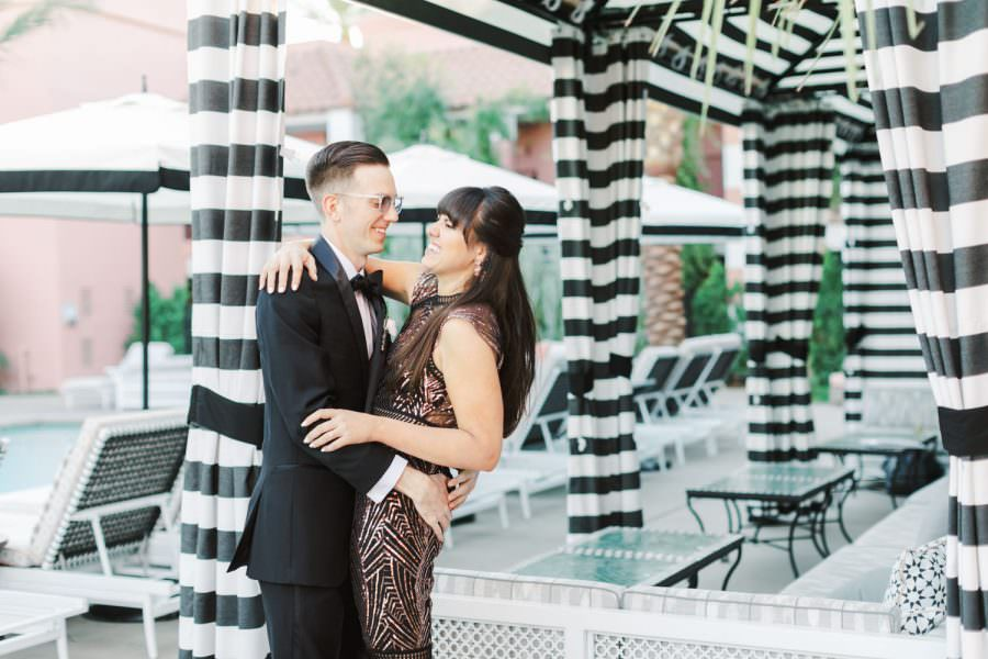 Black and white stripe cabana, Film engagement photo in a black and rose gold dress and black tux, Glamorous Sands Hotel Engagement Photos in Indian Wells, Cavin Elizabeth Photography