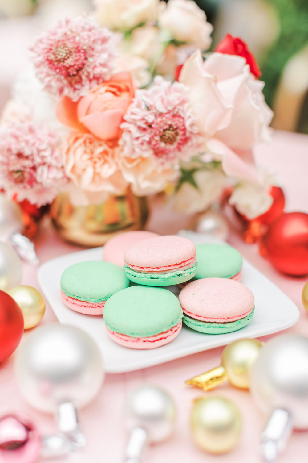 Chic Beverly Hills Hotel Bridal Shower cocktail table with pink drink and pink linens and pops of ivory and red in Los Angeles during Christmas decorations, pink and green macarons, Cavin Elizabeth Photography