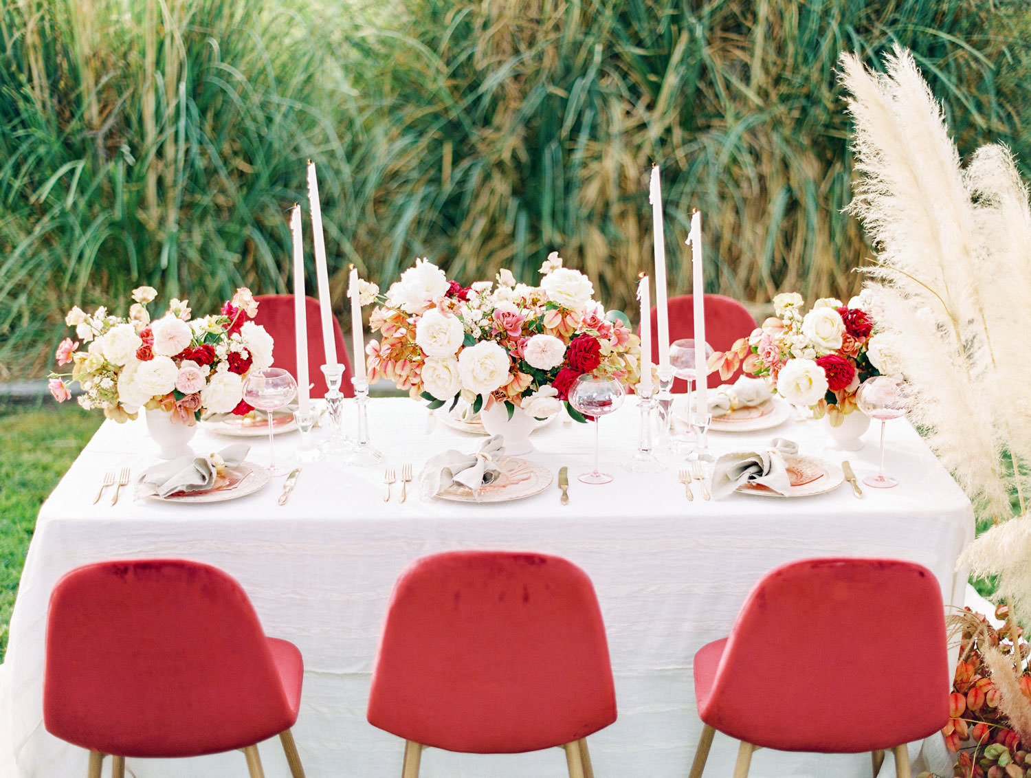 White linen with burgundy velvet chairs and centerpieces with ivory blush red and neutral tones, Pampas Grass Wedding in San Diego on Film by Cavin Elizabeth Photography