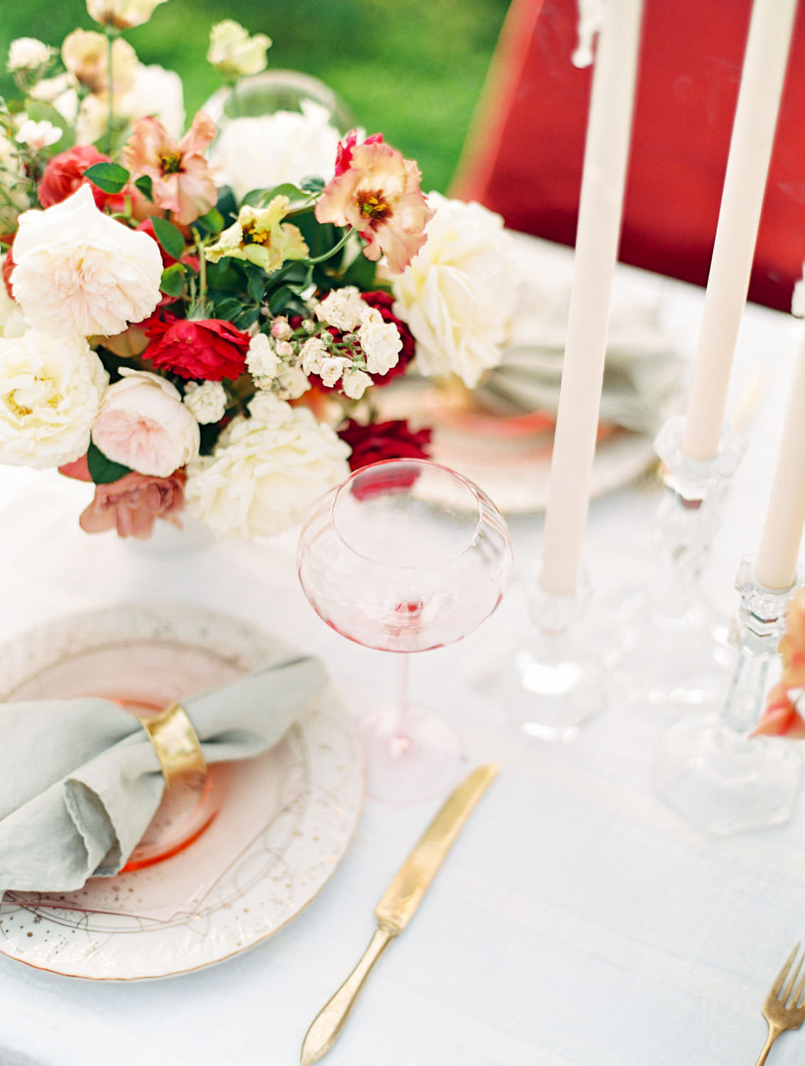 White linen with burgundy velvet chairs and centerpieces with ivory blush red and neutral tones, place setting with light pink plate and wine glass with a neutral charger with stars, Pampas Grass Wedding in San Diego on Film by Cavin Elizabeth Photography