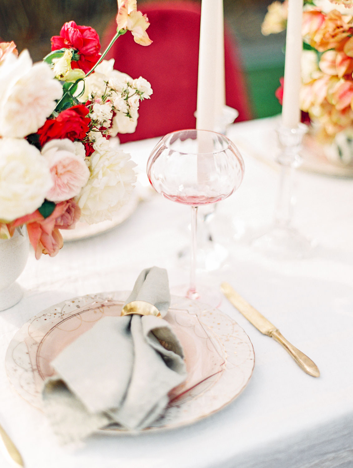 White linen with burgundy velvet chairs and centerpieces with ivory blush red and neutral tones, placesetting with light pink plate and wine glass with a neutral charger with stars, Pampas Grass Wedding in San Diego on Film by Cavin Elizabeth Photography