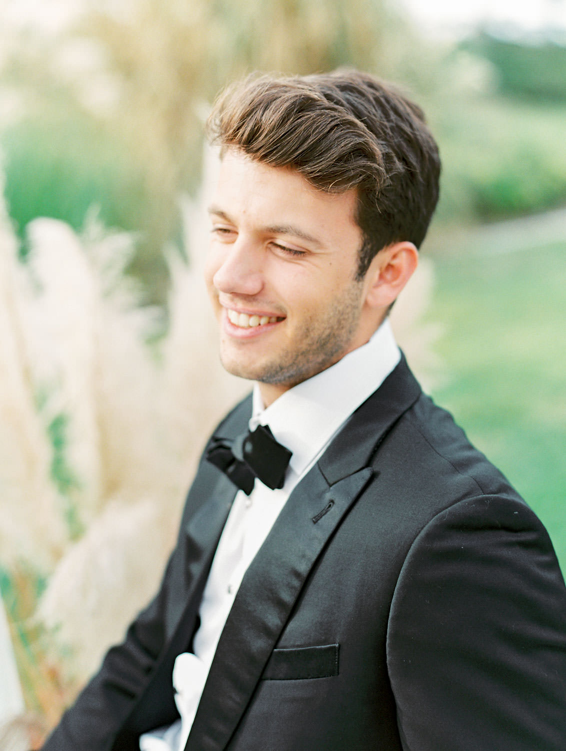Groom in The Black Tux sitting at reception table in a pampas grove, Pampas Grass Wedding in San Diego on Film by Cavin Elizabeth Photography