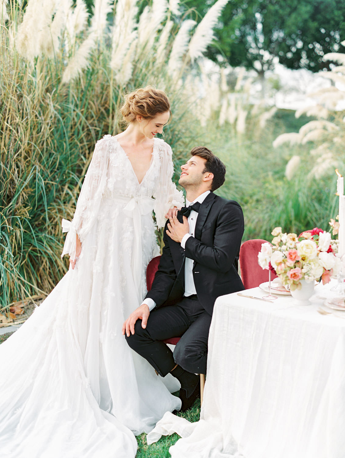Bride in Marchesa Poppy gown and groom in The Black Tux sitting at reception table in a pampas grove, White linen with burgundy velvet chairs and centerpieces with ivory blush red and neutral tones, Pampas Grass Wedding in San Diego on Film by Cavin Elizabeth Photography