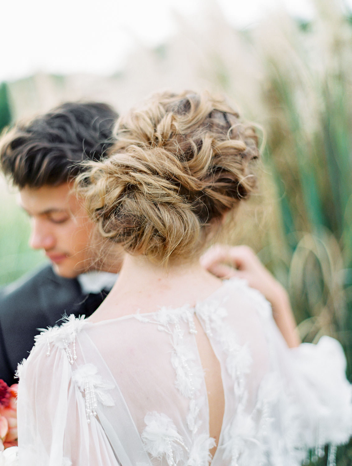 Close up portrait of bride's curled fine art soft updo in long sleeve Marchesa Poppy gown, beaded and feather embellished wedding dress, Pampas Grass Wedding in San Diego on Film by Cavin Elizabeth Photography