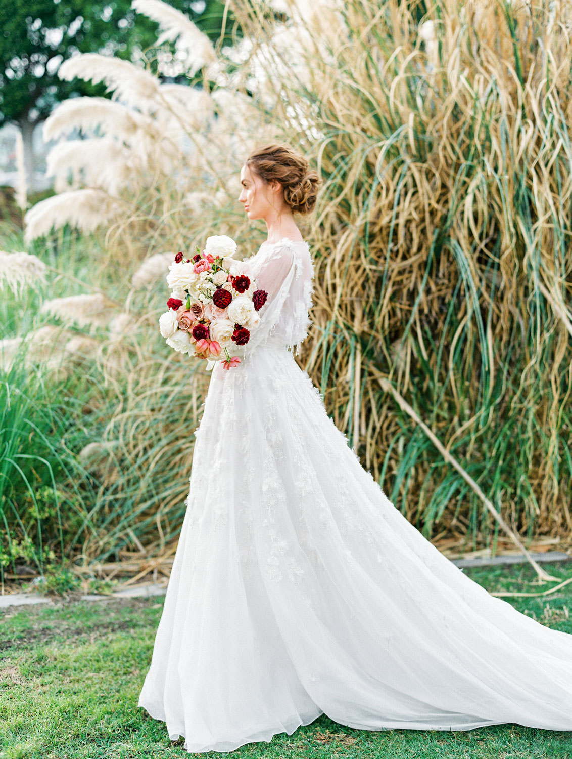 Full length portrait of bride with burgundy blush and ivory bouquet in long sleeve Marchesa Poppy gown, beaded and feather embellished wedding dress, Pampas Grass Wedding in San Diego on Film by Cavin Elizabeth Photography