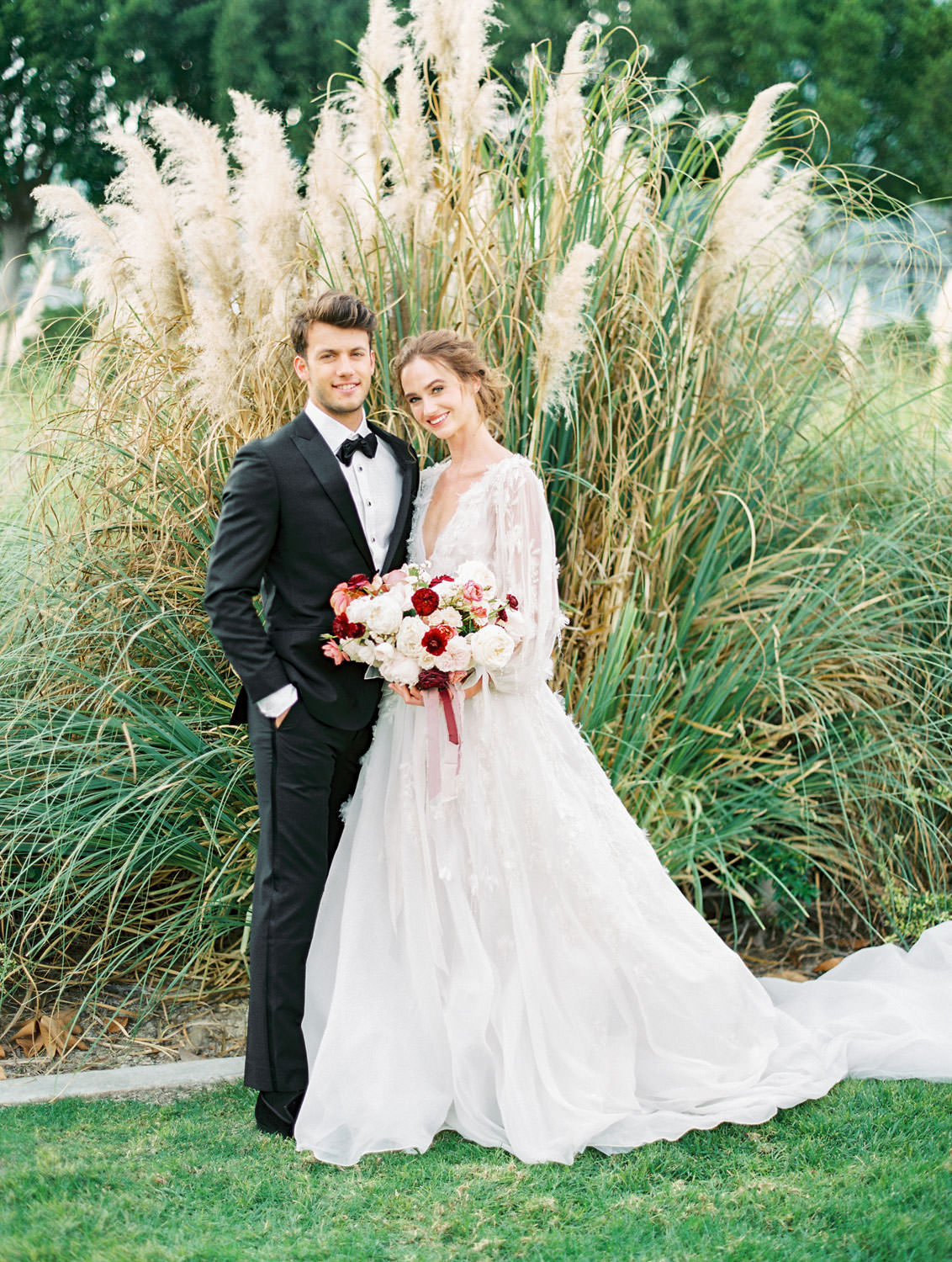 Groom in black tux and Bride with burgundy blush and ivory bouquet in long sleeve Marchesa Poppy gown, beaded and feather embellished wedding dress, Pampas Grass Wedding in San Diego on Film by Cavin Elizabeth Photography