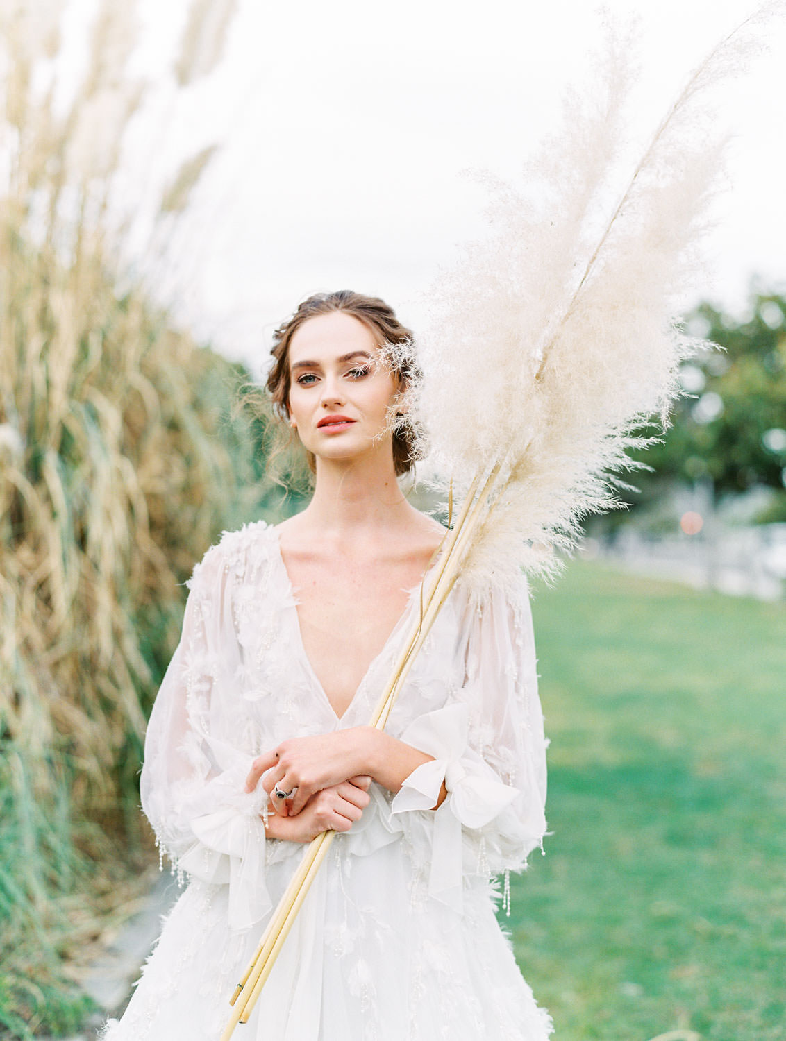 Bride with pampas grass in long sleeve Marchesa Poppy gown, beaded and feather embellished wedding dress, Pampas Grass Wedding in San Diego on Film by Cavin Elizabeth Photography